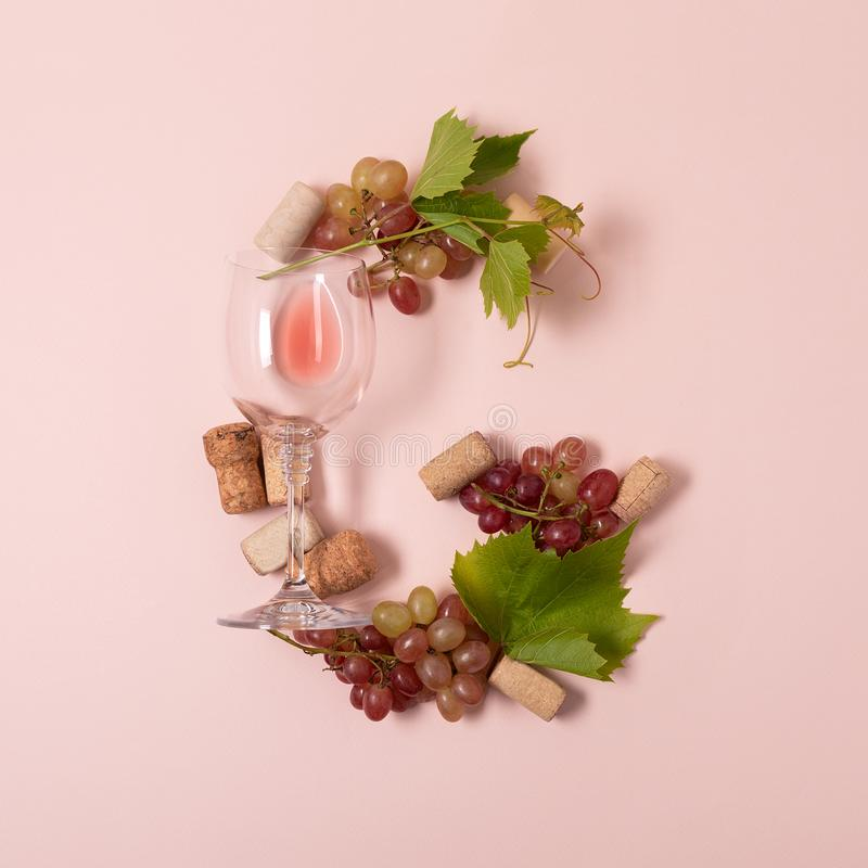 r Το γράμμα Γ φιαγμένο από wineglasses με το τριαντάφυλλο και το άσπρο κρασί, σταφύλια, αφήνει και βουλώνει να βρεθεί στο ρόδινο  στοκ φωτογραφία
