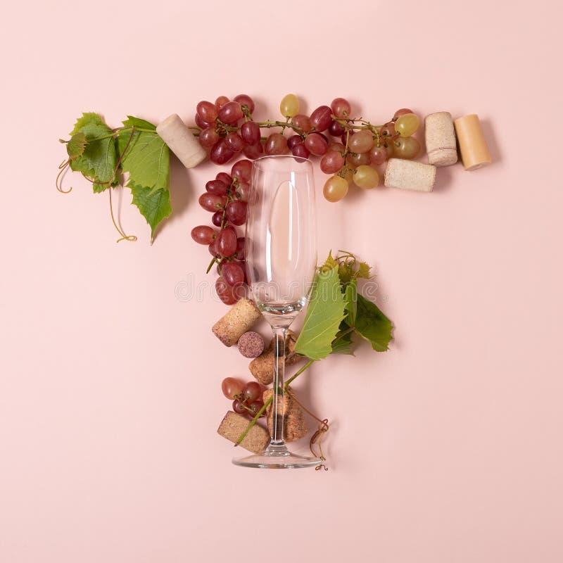 r Το γράμμα Τ φιαγμένο από wineglasses με το τριαντάφυλλο και το άσπρο κρασί, σταφύλια, αφήνει και βουλώνει να βρεθεί στο ρόδινο  στοκ φωτογραφίες