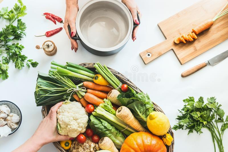 r Το θηλυκό χέρι προετοιμάζει τα διάφορα ζωηρόχρωμα οργανικά αγροτικά λαχανικά στο άσπρο υπόβαθρο γραφείων με το μαγείρεμα του δο στοκ εικόνα