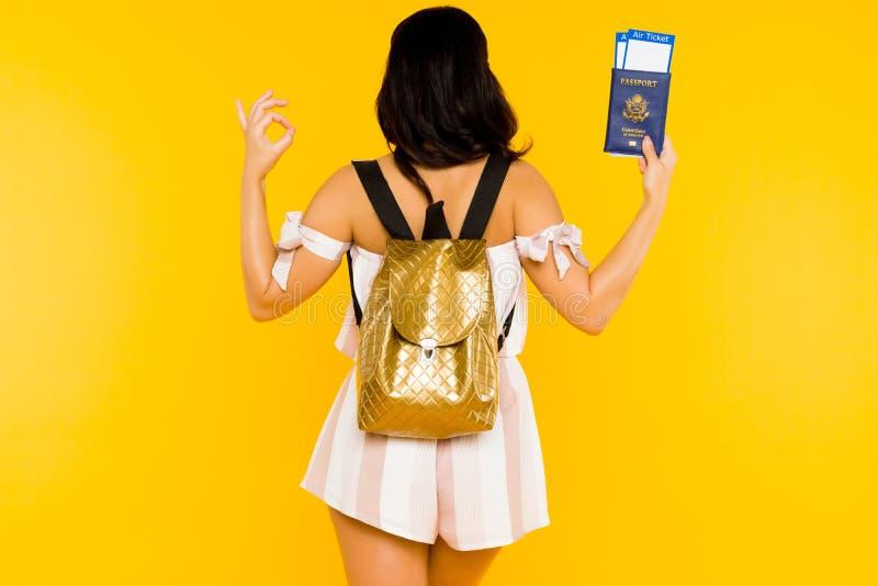 r Το νέο ασιατικό διαβατήριο εκμετάλλευσης γυναικών με τα εισιτήρια που στέκονται πίσω με το σακίδιο παρουσιάζει εντάξει σημάδι στοκ εικόνα με δικαίωμα ελεύθερης χρήσης