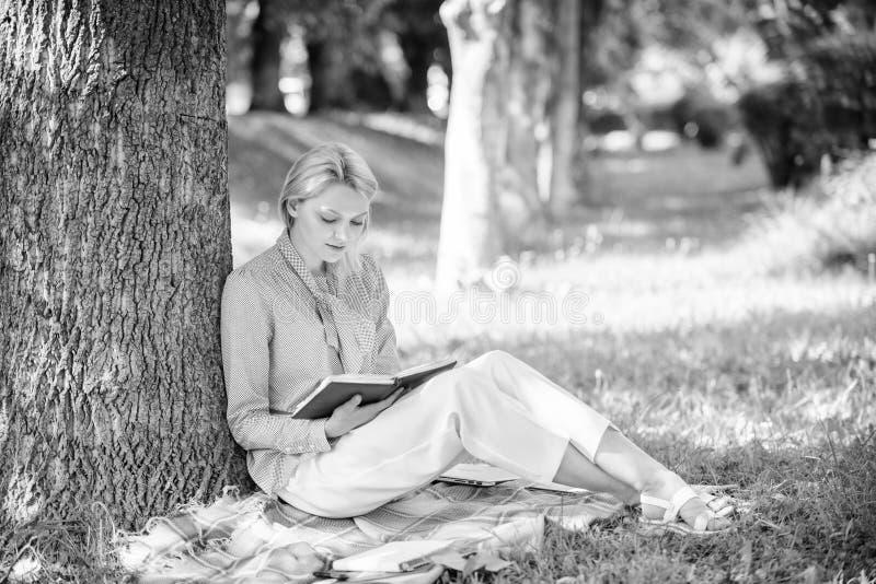 r Χαλαρώστε τον ελεύθερο χρόνο μια έννοια χόμπι E Το κορίτσι που συγκεντρώνεται το πάρκο κάθεται στοκ φωτογραφίες με δικαίωμα ελεύθερης χρήσης