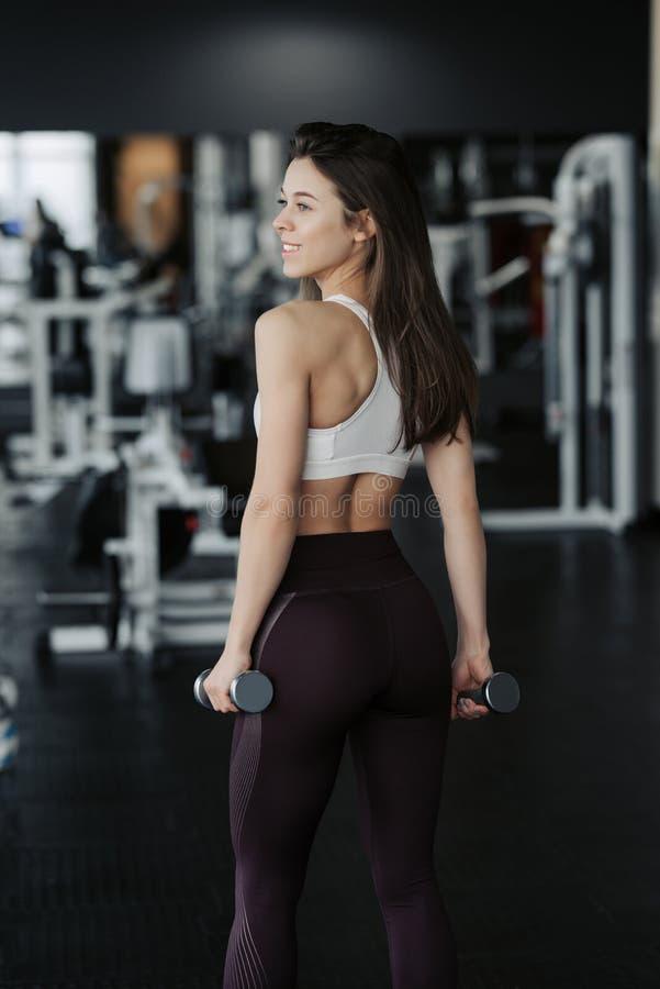r Атлетическая женщина фитнеса нагнетая вверх мышцы с гантелями Девушка фитнеса брюнета сексуальная в носке спорта с идеальным те стоковые изображения rf