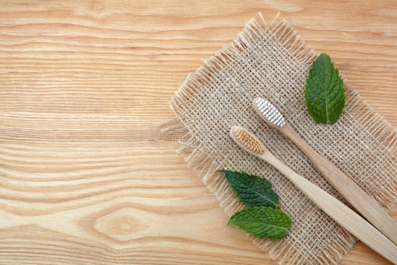 r Бамбуковая зубная щетка на деревянной предпосылке с зелеными лист мяты Пластиковые свободные предметы первой необходимости, заб стоковые изображения