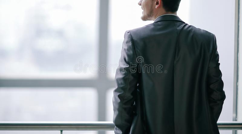 r бизнесмен в случайной носке стоя и думая около окна офиса стоковые изображения rf