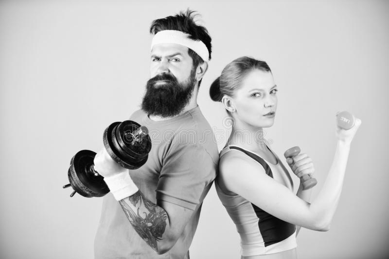 : r Гантели владением девушки и парня Тренировки спорта фитнеса sporty стоковая фотография