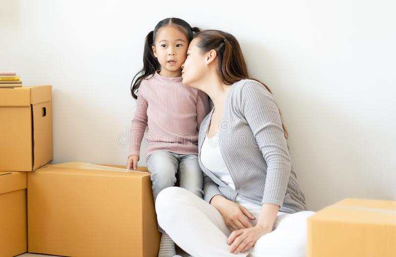 r Девушка матери и ребенка распаковывая картонные коробки, играя, целуя и обнимая для их нового дома Двигать стоковые изображения rf