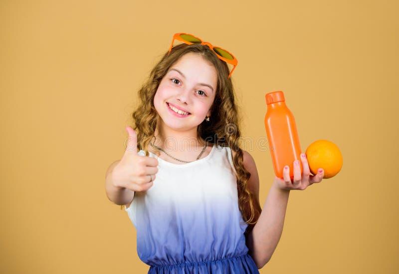 r Естественный источник витамина Девушка ребенк ест оранжевый плод и выпивает апельсиновый сок Питание витамина m стоковые фото