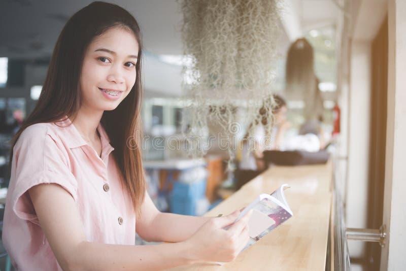 r Женщина сидя на столе используя умный телефон, смотря камеру, женщина Азии портрета красивая стоковое фото