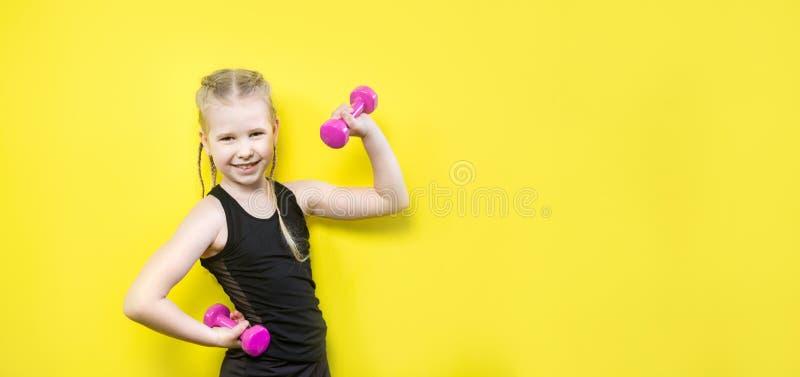 r Красивая кавказская девушка ребенка с отрезками провода представляя на желтой предпосылке с улыбкой маленький спортсмен стоковые изображения rf
