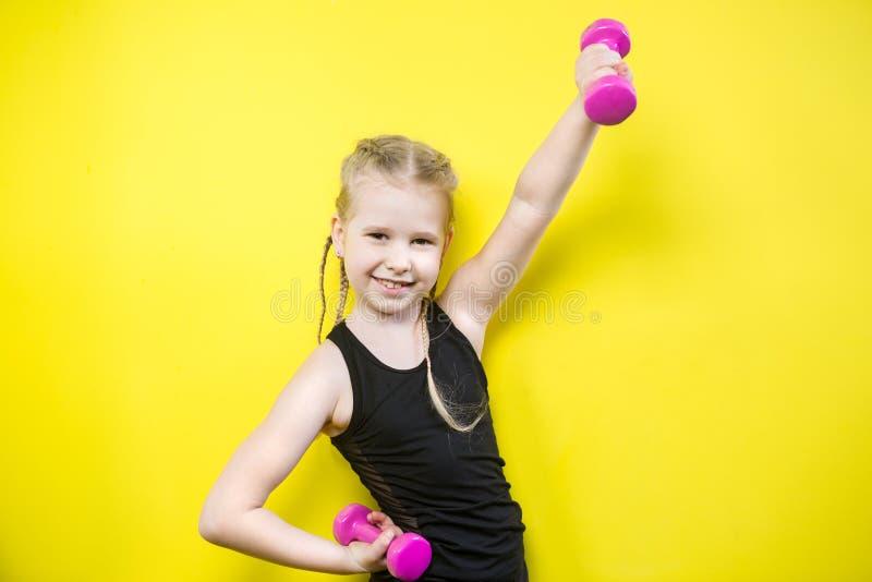 r Красивая кавказская девушка ребенка с отрезками провода представляя на желтой предпосылке с улыбкой маленький спортсмен стоковые фото