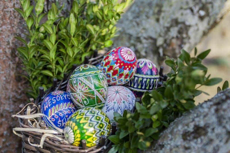 r Красочные пасхальные яйца в плетеной корзине стоковое изображение rf