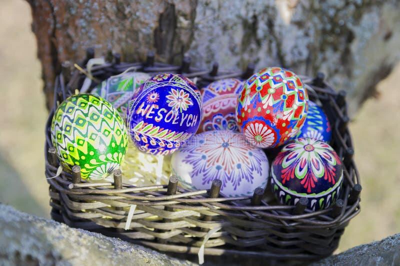r Красочные пасхальные яйца в плетеной корзине стоковые фото