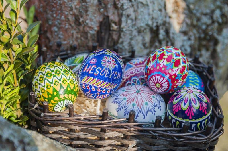 r Красочные пасхальные яйца в плетеной корзине стоковое изображение