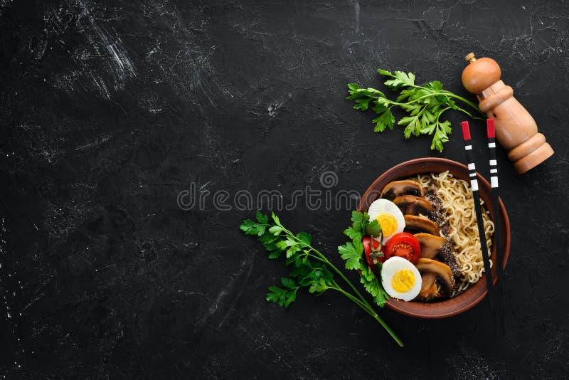 r Лапши с грибами, яйцами и семенами chia На черной каменной предпосылке стоковое фото rf