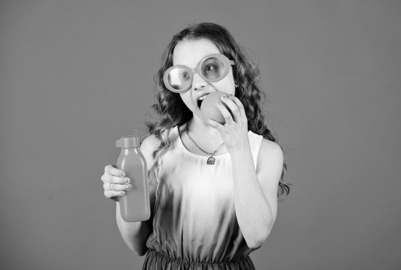 r маленькая девочка в стеклах моды Питание витамина освежая сок витамина r o стоковая фотография rf