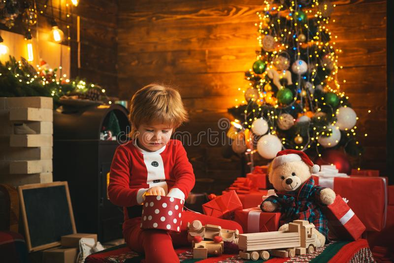 r r Мальчик Санта празднует рождество дома Детская игра мальчика около рождественской елки Веселый и стоковые изображения