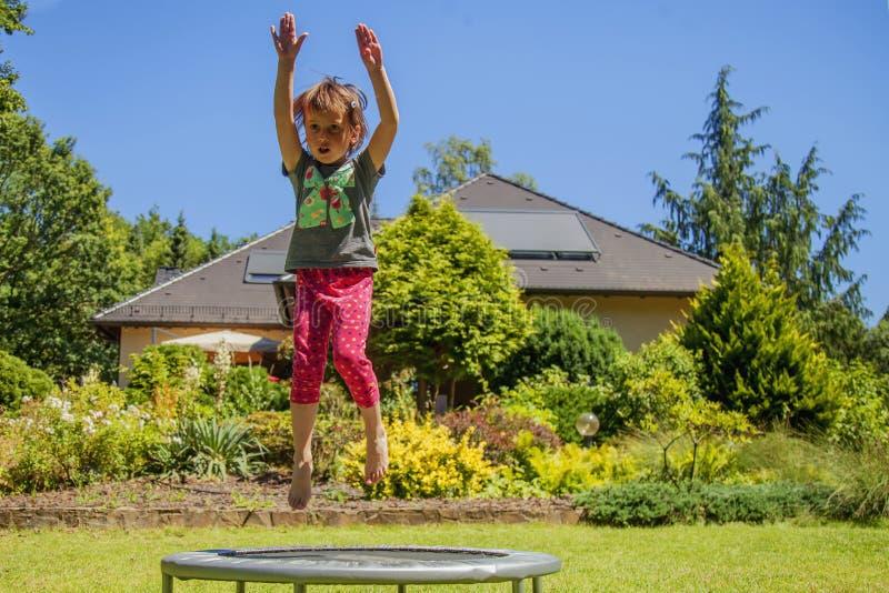 r Меньшая очень счастливая милая девушка ребенка наслаждается поскакать на батут Горизонтальное изображение стоковые изображения rf