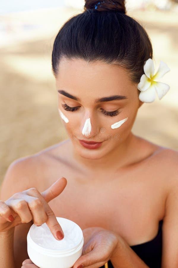r Модель женщины с естественным макияжем и здоровой кожей Портрет красивой девушки с улыбкой держа косметическую сливк в tro стоковые фото