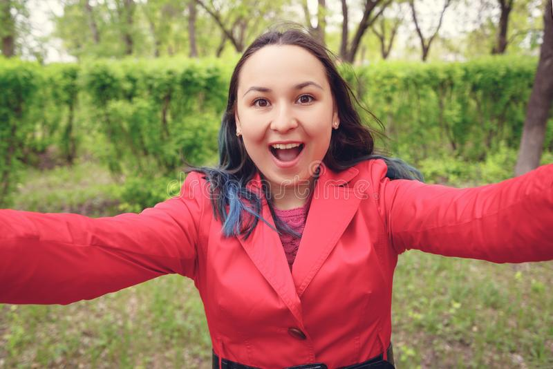r Молодая женщина в красных одеждах на улице принимает selfie, смотрит камеру и улыбки стоковая фотография rf