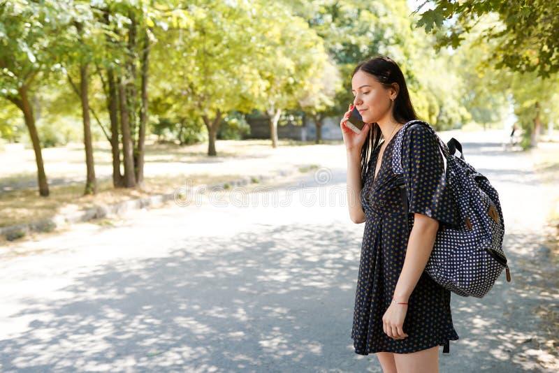 r Молодая случайная женщина с умным телефоном и сумка около автомобиля дороги ждать стоковые фото