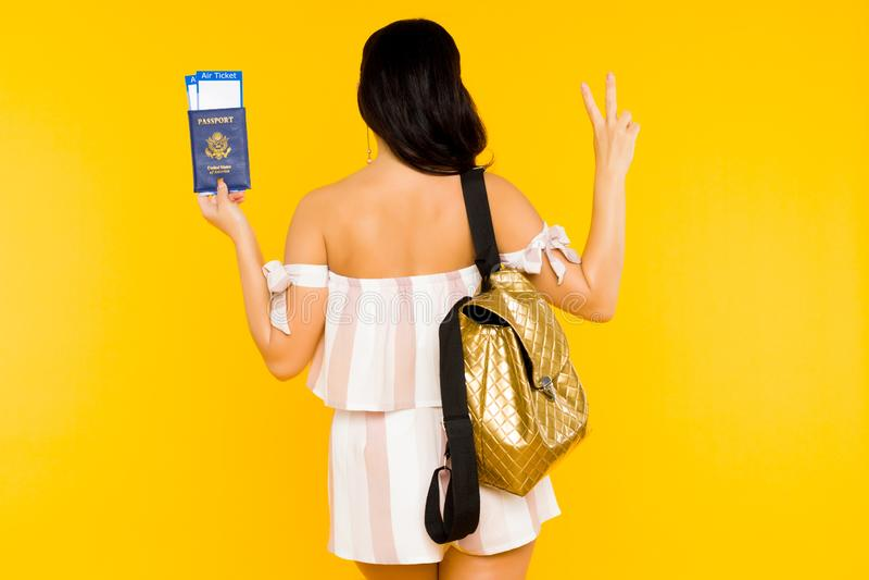 r Молодой азиатский паспорт удерживания женщины с билетами стоя назад со знаком мира шоу рюкзака стоковые фото