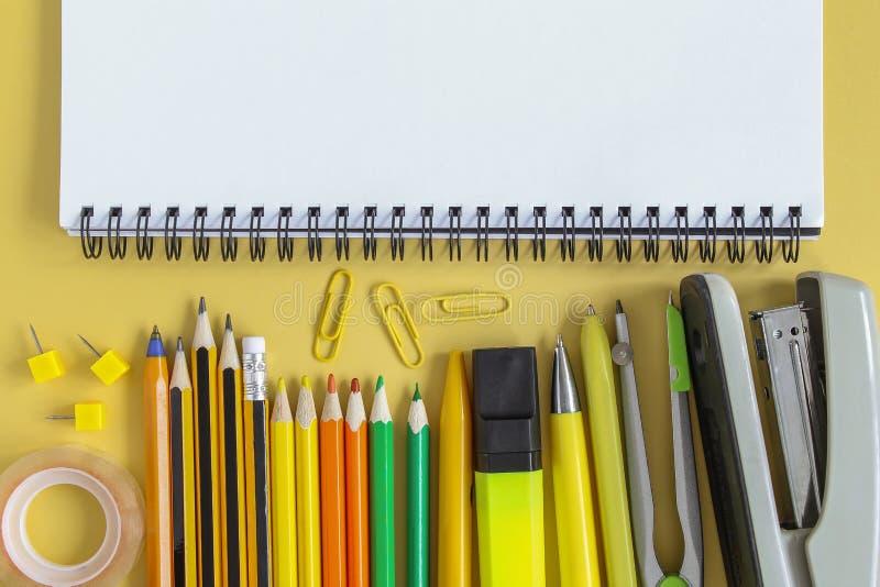 r Открытая пустая тетрадь модель-макета и покрашенные канцелярские принадлежности школы Желтая бумажная предпосылка Плоское полож стоковые фотографии rf