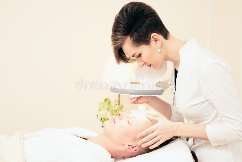 r офис cosmetologist косметологии рассматривает кожу маленькая девочка лежа на кресле стоковые фото