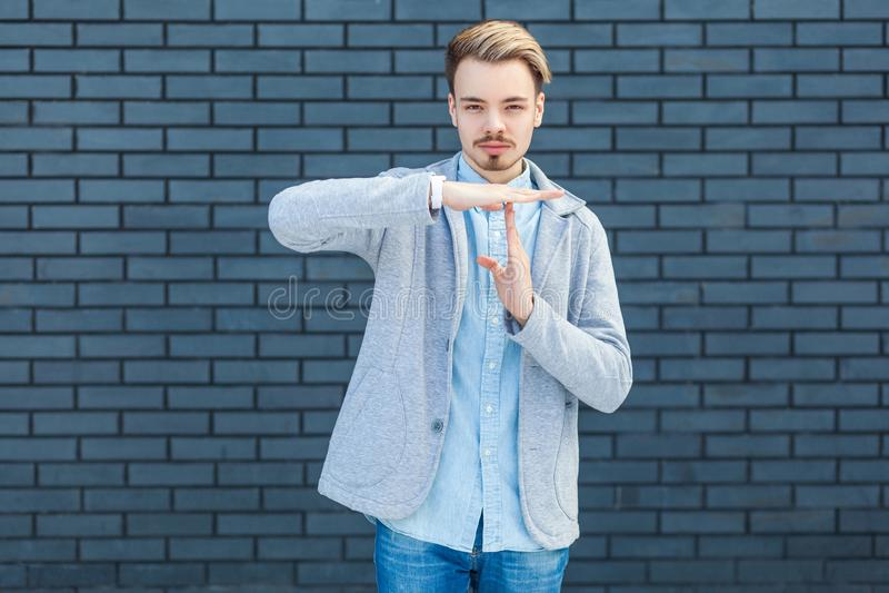 r Портрет серьезного красивого молодого белокурого человека в непринужденном стиле стоя с рукой жеста перерыва и смотря камеру с стоковое изображение