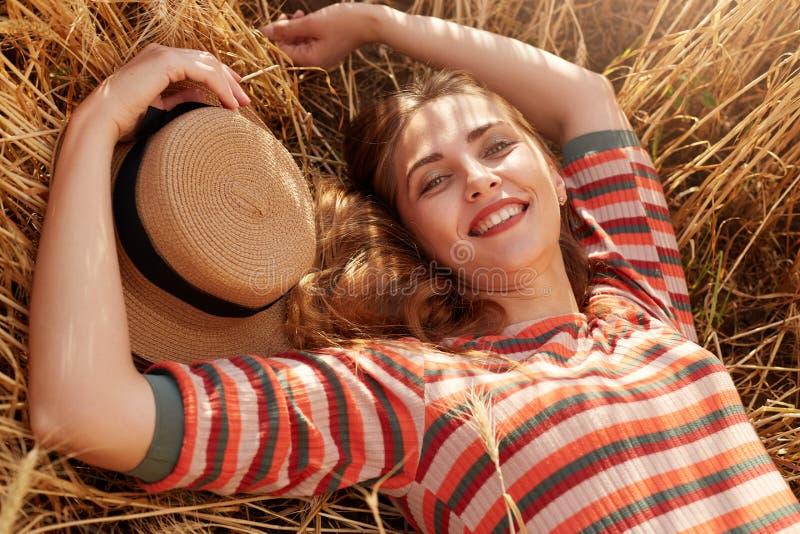 r Привлекательная счастливая молодая женщина в striped платье и соломенной шляпе кладя на землю стоковые фотографии rf