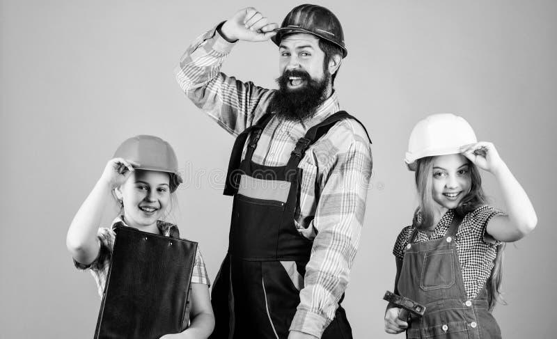 r Сестры помогают построителю отца Домашняя реновация Создайте комнату вы действительно хотите в реальном маштабе времени Следова стоковая фотография