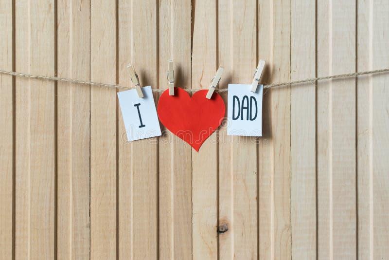 r Сообщение с бумажным сердцем вися со штырями над светлой деревянной доской r стоковое изображение rf