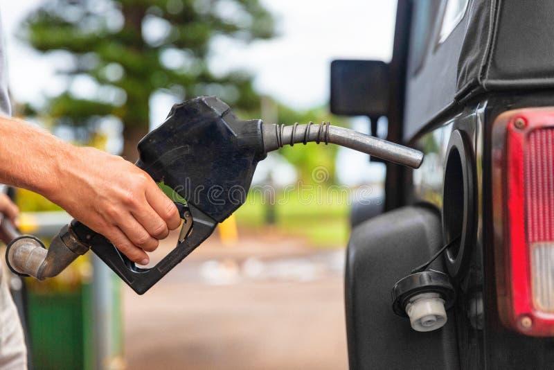r Топливо бензина человека заполняя в сопле удерживания автомобиля стоковая фотография