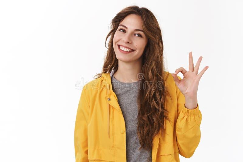 r Усмехаться знака утверждения ок ок шоу волос каштана милой беспечальной современной стильной кавказской девушки длинный зубасты стоковые фото
