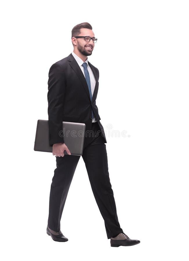 r усмехаясь бизнесмен с ноутбуком шагая вперед стоковые изображения rf