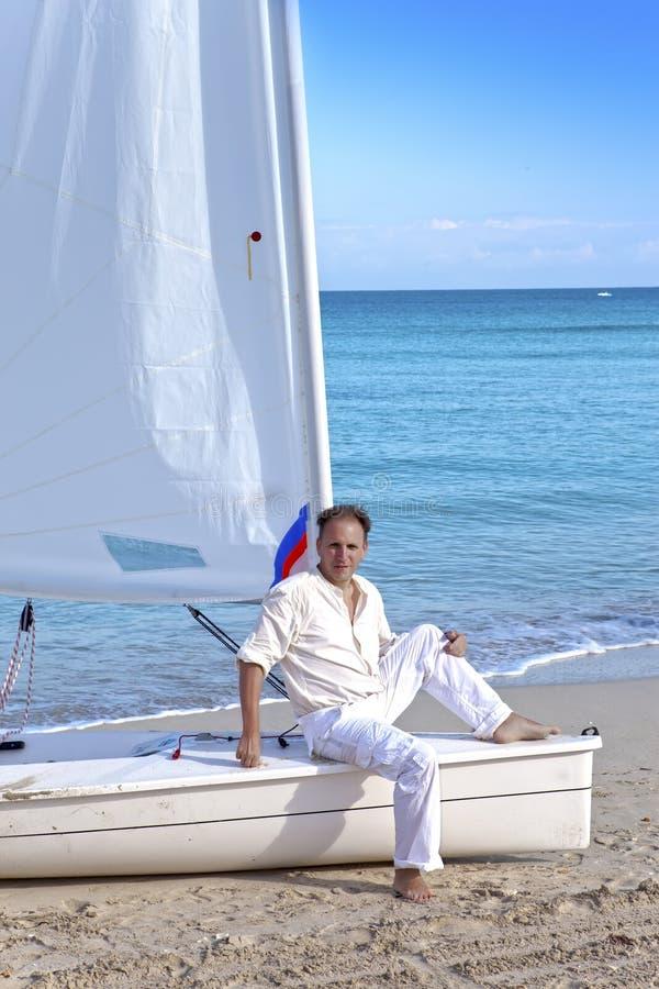 r Человек на голубом море рядом со шлюпкой с ветрилом стоковые изображения rf