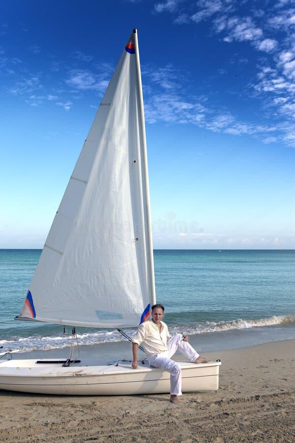 r Человек на голубом море рядом со шлюпкой с ветрилом стоковые изображения