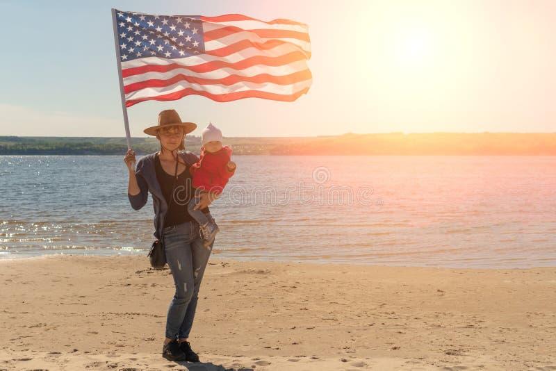 r r 一个牛仔帽的一名妇女有她的胳膊的一个婴孩的和有一面美国国旗的 库存图片