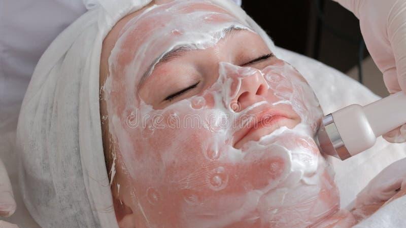 r 一名美容师的手白色手套的使用按摩用具的电极在a的面孔的 图库摄影