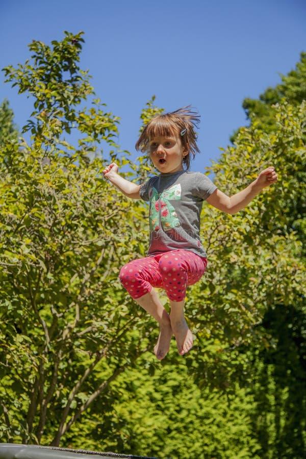 r 一点获得逗人喜爱的儿童跳跃为在绷床的喜悦的女孩乐趣户外和她 免版税库存图片