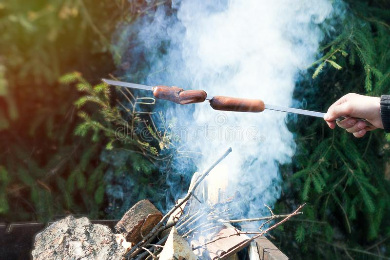 r 不正确烹调在火的香肠:熏制的香肠没有通过里面被烹调 库存图片