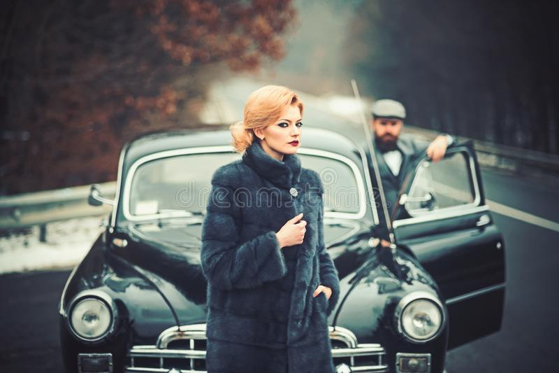 r 乡情和减速火箭的汽车在有胡子的男人和妇女外套的 免版税图库摄影