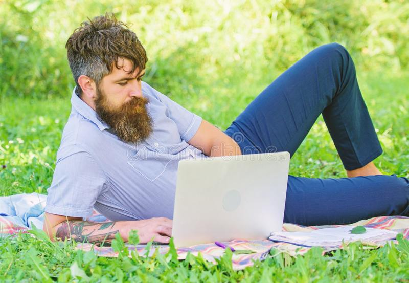 r 人有胡子有膝上型计算机放松的草甸自然背景 寻找启发的作家 免版税图库摄影