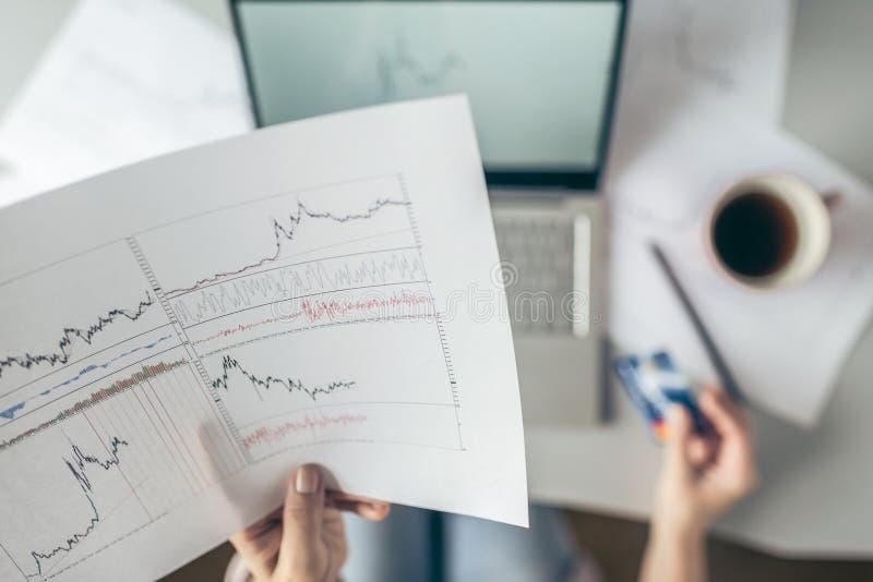 r 使用膝上型计算机和信用卡的妇女为买在网上在证券交易所 薪水和商务 ?? 图表和图 免版税图库摄影