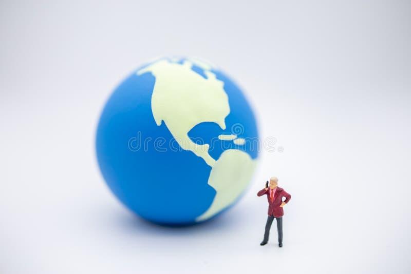 r 关闭商人微型形象身分并且打与微型世界球的一个电话  免版税库存图片