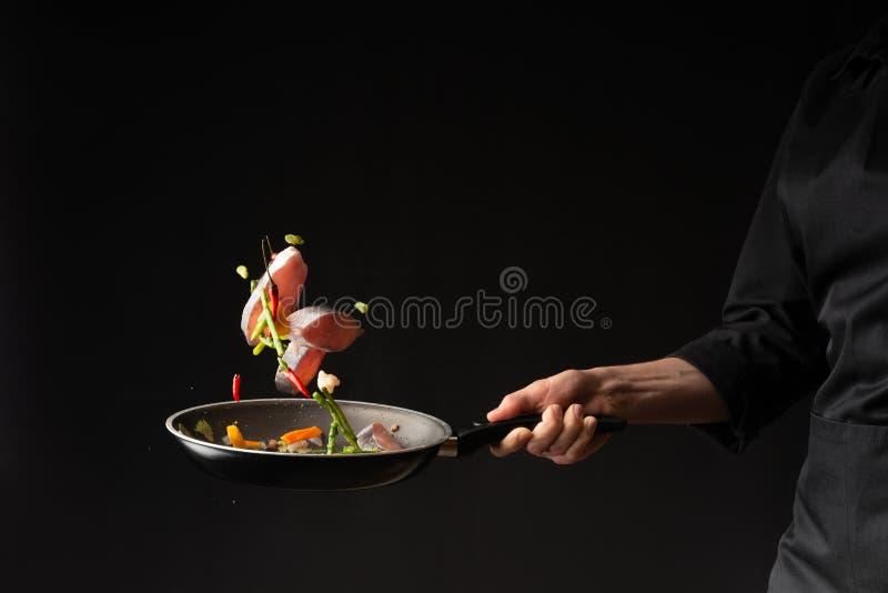 r 厨师厨师与菜的油炸物鱼在黑背景的一个平板炉 r ?? r 库存图片