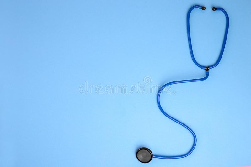 r 听诊器特写镜头在蓝色背景的 听与听诊器的心脏 r 图库摄影