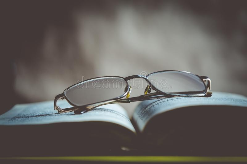 r 在书的玻璃 开放作嘘声 库存照片