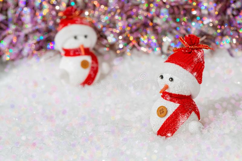 r 在他们的雪人红色帽子和围巾 在白雪的雪人在五颜六色的光亮的bokeh背景旁边 图库摄影