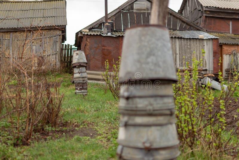 r 在彼此安置的老金属桶金字塔在庭院 库存照片