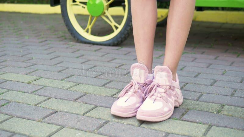r 在时髦的桃红色运动鞋的女性腿 走在有路面的街道上的女孩 自然晴朗的白天 免版税库存图片